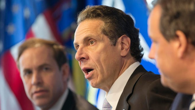 "New York Gov. Andrew Cuomo, center, speaks at a news conference Friday in New York. At left is Dr. Howard Zucker, acting commissioner of the New York State Department of Health, and New Jersey Gov. Chris Christie is at right. The governors announced a mandatory quarantine for people returning to the United States through airports in New York and New Jersey who are deemed ""high risk."" In the first application of the new set of standards, the states are quarantining a female healthcare worker returning from Africa who took care of Ebola patients."