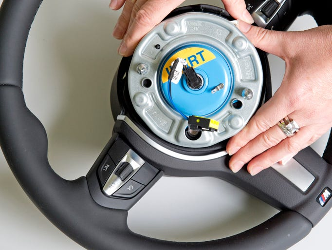 A worker demonstrates a Takata pyro-electric wheel