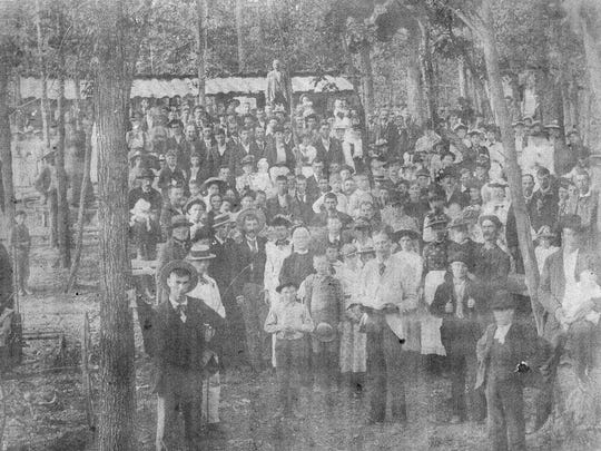 Green Berry Jones, front, holding book and in a light-colored jacket stands amidst a crowd at what appears to be a camp meeting.