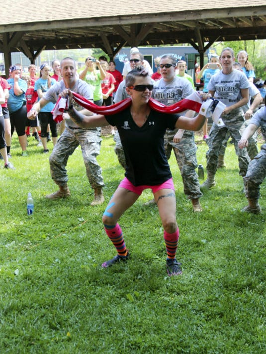 """Guest speaker Laura Wilkinson leads a group in the """"22 Challenge"""" during the annual Indian Dash Mud Run Saturday to benefit the Wounded Warrior Project. Wilkinson is a U.S. Army veteran and a cancer survivor, and was among dozens who turned out get dirty at the event organized by Waynesboro students."""