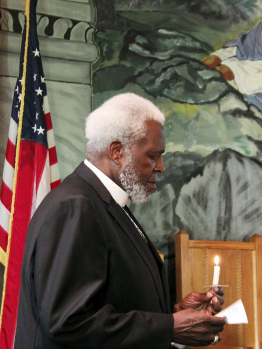 Rev. Dr.  Allie J.  Harper Jr. lights a candle for victims of the Charleston, S.C. mass shooting Sunday. About 60 people came together at the St. James African Methodist Episcopal Church, 510 S. Main St., Chambersburg, for a prayer vigil.
