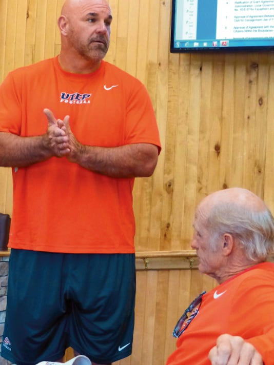 Head football coach Sean Kugler, standing, and Nate Poss, assistant athletic director for football at the University of Texas, El Paso, told village councilors how much they appreciated their welcome for summer training from residents and officials in the village.