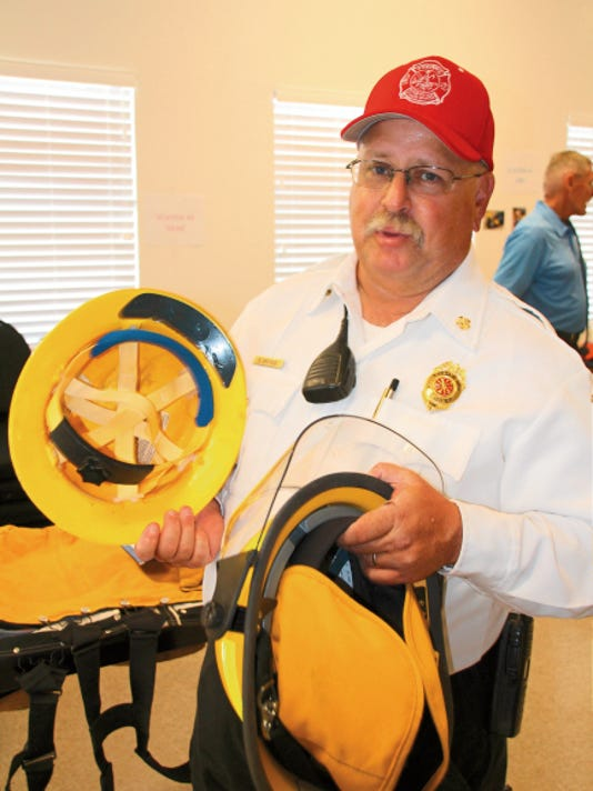 Tyrone Volunteer Fire Department Chief shows the different between a wildfire helmet on the left and a structural fire helmet, which gives thermal protection, on the right, during Saturday's open house at the newly expanded Tyrone Fire Department. Mary Alice Murphy - Sun-News