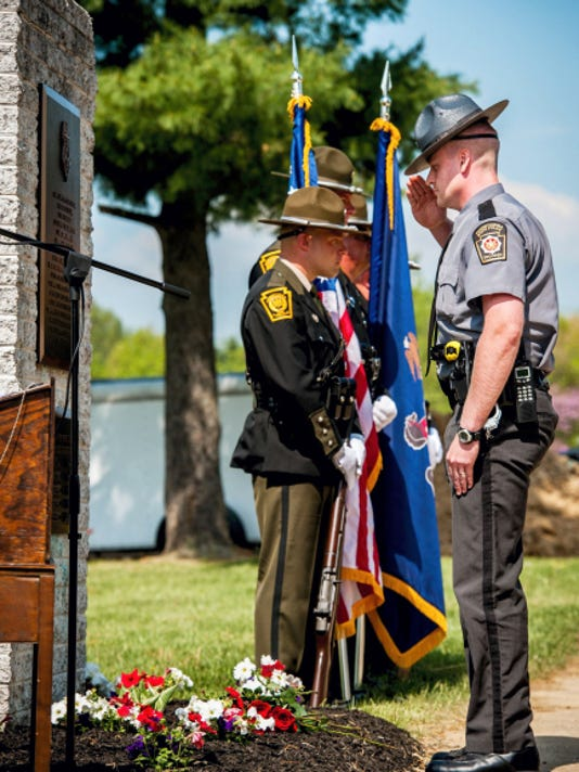 Pennsylvania State Police Trooper George Ross salutes after placing a rose in memory of fallen State Police Cpl. Byron Dickson, who was shot outside the Blooming Grove Road barracks last September, during the annual Adams County Fallen Police Officers Memorial ceremony at Oak Lawn Cemetery in Cumberland Township on May 8.
