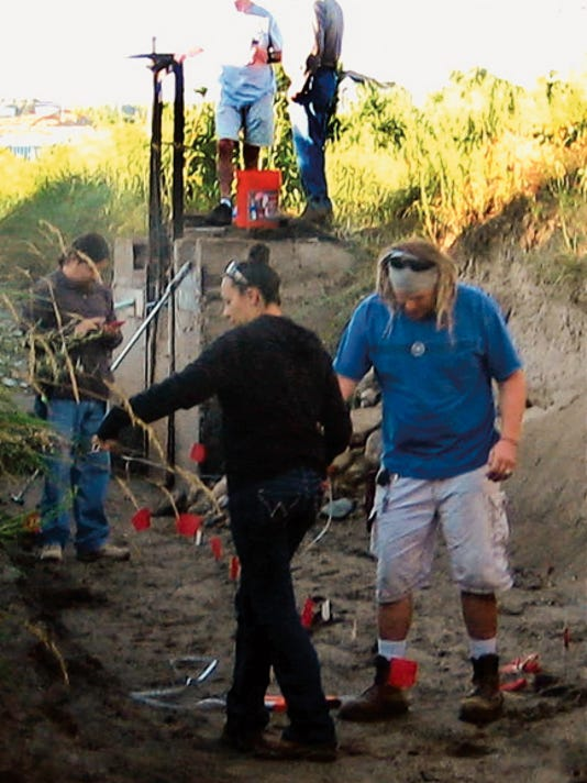 New Mexico State University employees from the Agricultural Science Center at Farmington help to take soil samples in San Juan County irrigation ditches while gates are closed. The gates had been closed prior to the Gold King Mine spill plume in the Animas River reached the county.