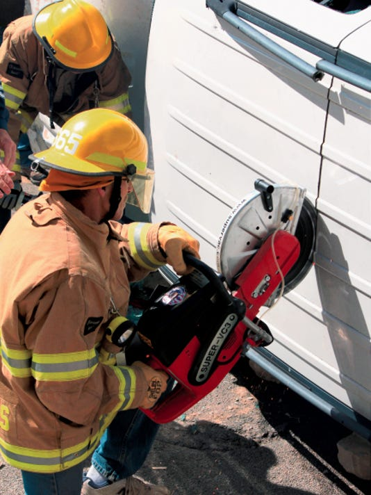 A firefighter from the High Rolls Volunteer Fire Department used a circular saw to cut into the roof of a Jeep Liberty that rolled over on U.S. Highway 82 near mile marker 4. Workers switched to a hydraulic cutting tool because of concerns that sparks from the saw might ignite gasoline leaking from the vehicle.
