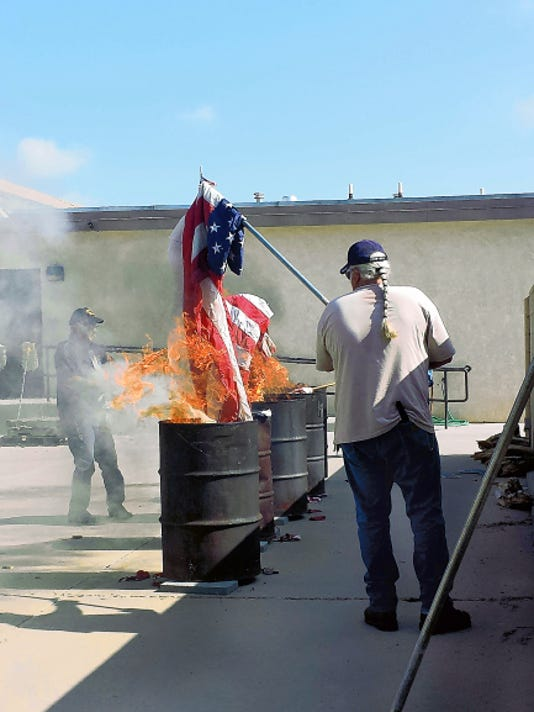 Photo Courtesy of the American Legion Post 7   Bob Walker, American Legion Rider, Chapter 3 Commander carries a flag over to one of the barrels to properly dispose of it.