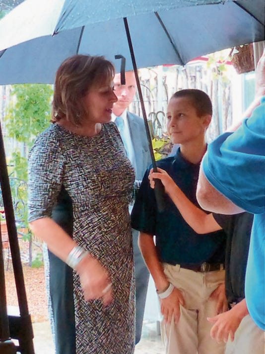 Shielded from a torrential downpour during a Ruidoso mountain thunderstorm, Gov. Susana Martinez thanks a young admirer for the coverage.