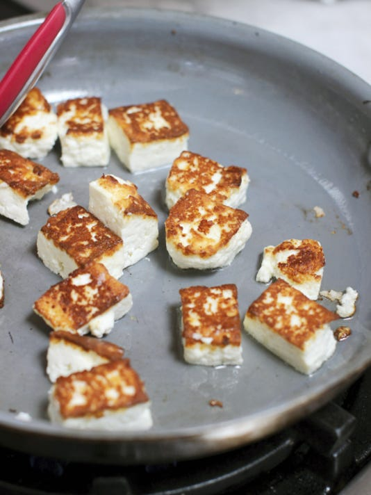Brown cubes of fresh cheese before combining them with greens in a creamy sauce. (AP Photo/Matthew Mead)