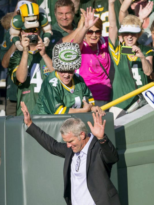 Former Green Bay Packers quarterback Brett Favre waves to fans as he walks onto Lambeau Field prior to getting inducted in to the Packers Hall of Fame and having his No. 4 jersey retired, Saturday, July 18, 2015, in Green Bay, Wis.