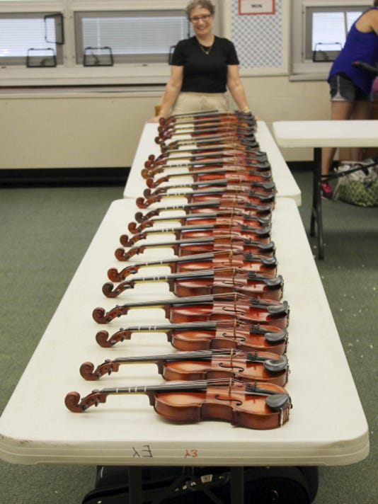 Mindy Jo Hamme stands with some of the instruments she helped raise money to purchase for students in the York Suburban School District.