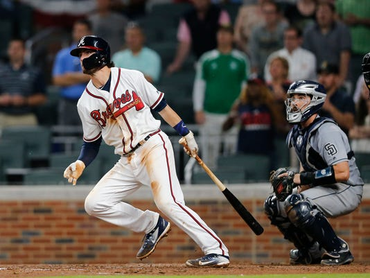 Atlanta Braves' Dansby Swanson drives in the game-winning run with a base hit as San Diego Padres catcher Austin Hedges (18) looks on in the ninth inning of a baseball game against the San Diego Padres, Monday, April 17, 2017, in Atlanta. Atlanta won 5-4. (AP Photo/John Bazemore)