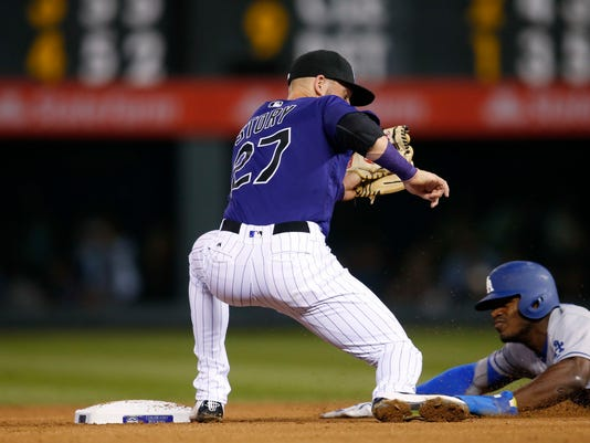 Colorado Rockies shortstop Trevor Story, left, misses the throw as Los Angeles Dodgers' Yasiel Puig steals second base during the fourth inning of a baseball game Friday, April 22, 2016, in Denver. Colorado won 7-5. (AP Photo/David Zalubowski)