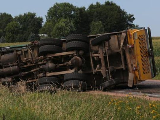 A heavy-duty truck lies on its side at the scene of