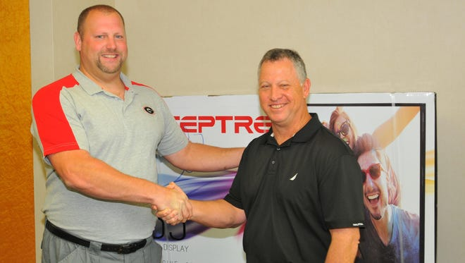 Mike Fredenburg, left, is congratulated by Jeff Kiel, president and publisher of FLORIDA TODAY, for winning the FLORIDA TODAY High School Football Picks Challenge. Fredenburg won a 55-inch TV, which can be seen behind them.