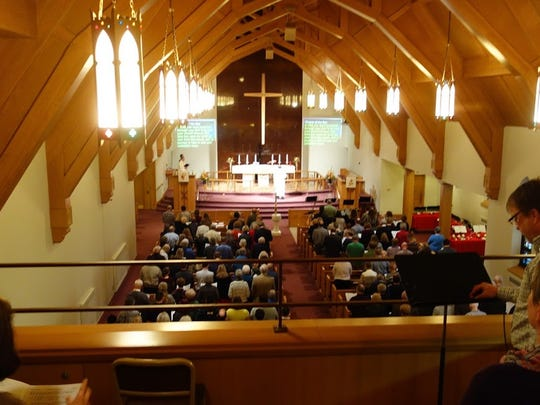 Congregation members celebrate the final Sunday service at Trinity Lutheran Church in downtown Appleton on Nov. 20. The church is moving to a temporary location after selling its property to a developer.