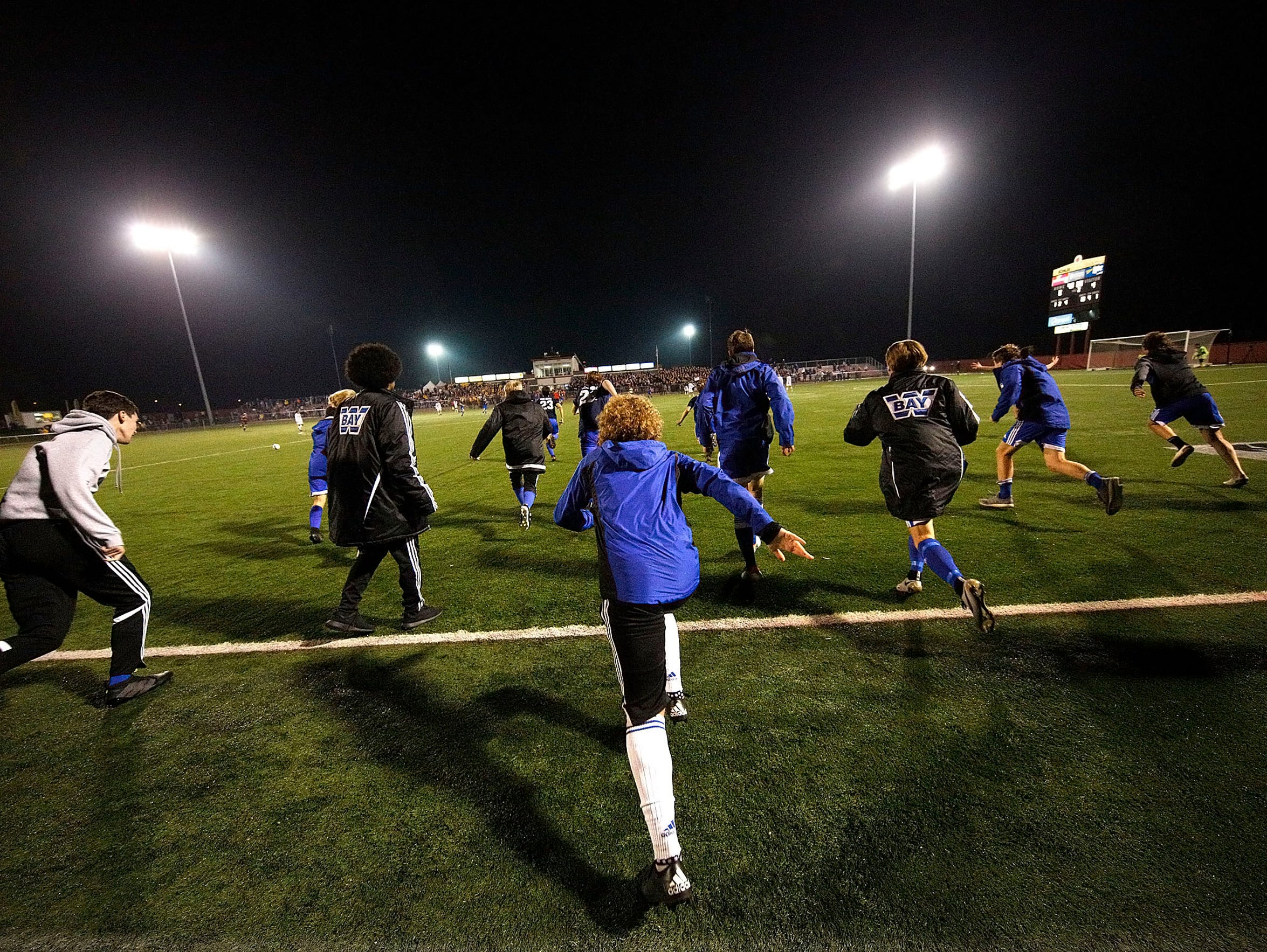 Bay soccer players rush the field following their victory