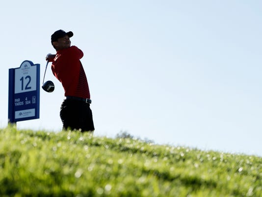Tiger Woods watches his tee shot on the 12th hole of the South Course at Torrey Pines Golf Course during the final round of the Farmers Insurance Open golf tournament, Sunday, Jan. 28, 2018, in San Diego. (AP Photo/Gregory Bull)