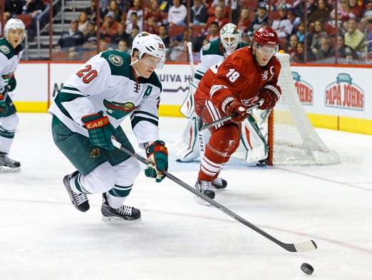 Minnesota Wild defenseman Ryan Suter (20) and Coyotes right wing Shane Doan (19)  chase down a puck during the first period of their NHL game Sunday, March 29, 2014 in Glendale, Ariz.