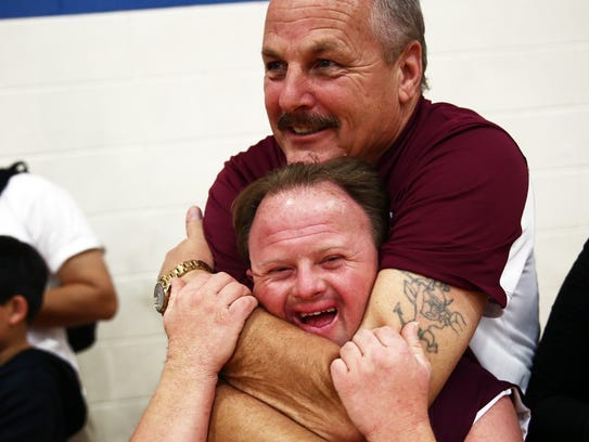 Coach Roger Jacobsen embraces player Kevin Kennedy while watching their team play in the Special Olympics state basketball tournament in Tavares on Saturday, Jan. 30, 2016. (Photo: Dorothy Edwards/Staff)