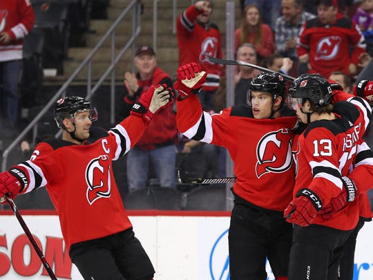The New Jersey Devils celebrate a goal by New Jersey Devils left wing Taylor Hall (9) during the second period of their game against the Calgary Flames at Prudential Center.