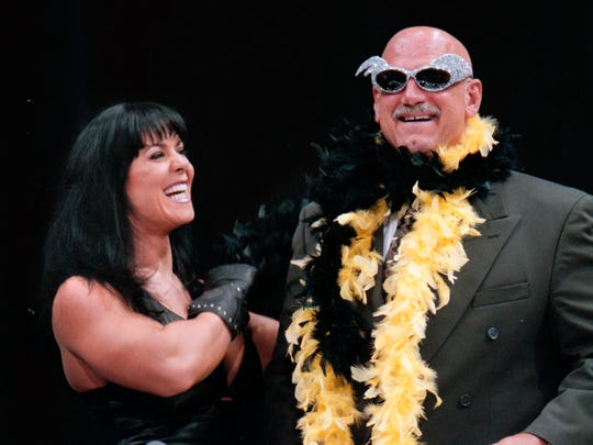 In this 1999 file photo, Minnesota Gov. Jesse Ventura is adorned with his signature feather boa and glitter sunglasses by Chyna during a World Wrestling Federation press conference at the Target Center in Minneapolis.