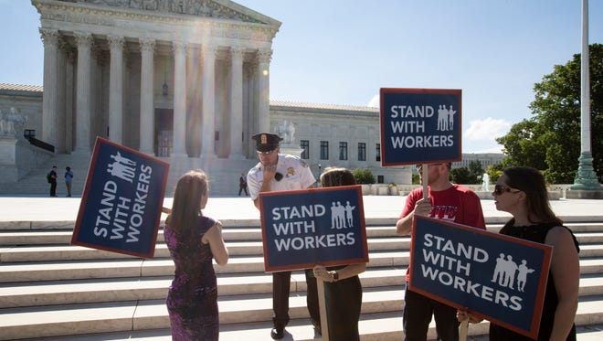 People gather at the Supreme Court awaiting a decision in an Illinois union dues case, Janus vs. AFSCME, in Washington, Monday, June 25, 2018. The outcome of that case and several others were not announced Monday as the court's term comes to a close. (AP Photo/J. Scott Applewhite)