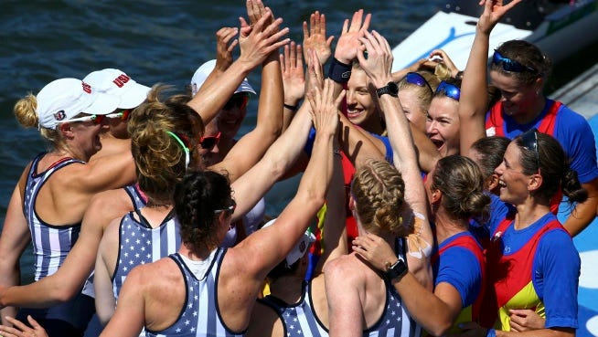 The women's rowing teams from the United States, left, and Romania celebrate on the dock after winning medals in the women's eight event at Lagoa in Rio de Janeiro, Brazil, Saturday, Aug. 13, 2016. Romania took the bronze, the United states the gold and Britain the silver.