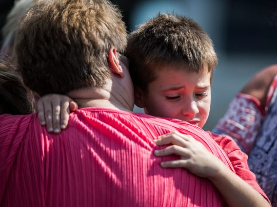 A child is hugged as he is picked up from Oakdale Baptist Church after a shooting in September at Townville Elementary School.