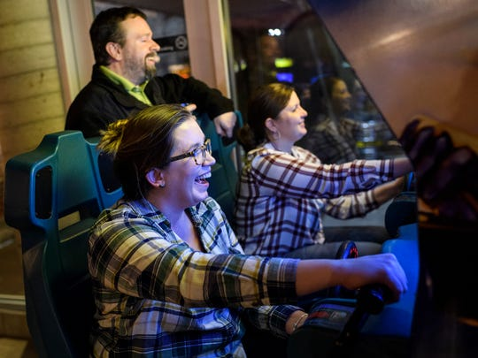 Shawnta Roebling (front) and Angela Edwards (back right) compete against each other while playing Hydro Thunder, a speedboat racing arcade game, as Robert Evans (back left) laughs along with them at High Score Saloon in Evansville. After finishing up their work day at Windstream Communications, the group came to the arcade to unwind while drinking High Score Saloon Arcade Ale, a Red Irish Ale made by local Carson's Brewery.