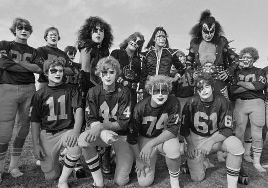 The band Kiss poses with members of the Cadillac High