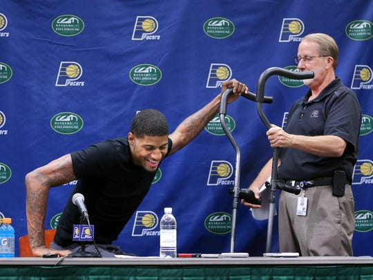 Pacers forward Paul George gets help from David Benner, Director of Media Relations, with his crutches after fielding questions about his recovery and future with the Pacers, Aug. 15, 2014.