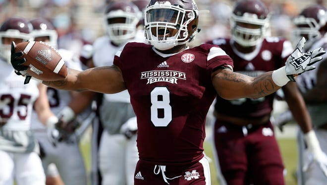 Maroon running back Kylin Hill (8) celebrates a touchdown run during the first half of Mississippi State's Maroon and White spring NCAA college football game Saturday, April 21, 2018, in Starkville, Miss. (AP Photo/Rogelio V. Solis)