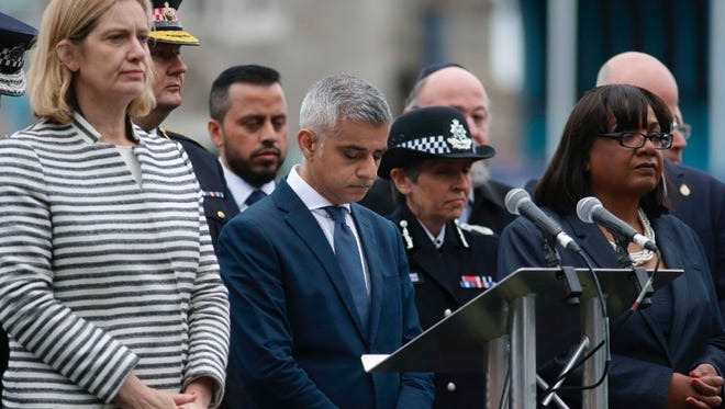 London Mayor Sadiq Khan bows his head flanked by Home Secretary Amber Rudd, left, and Shadow Home Secretary Diane Abbott, far right, during a vigil in Potters Fields Park in London on June 5 to commemorate the victims of the terror attack on London Bridge and at Borough Market that killed seven people on June 3.