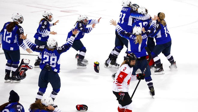 Canada's Meghan Agosta(2) skates away as the United States players celebrate after winning the women's gold medal hockey game against Canada at the 2018 Winter Olympics in Gangneung, South Korea, Thursday, Feb. 22, 2018.