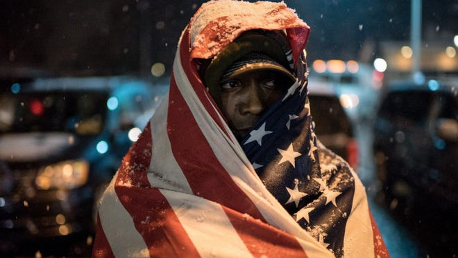 A protester stands in front of the Ferguson Police Department as the snow falls Nov. 26, 2014.