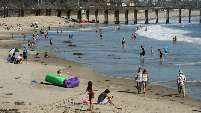 People spend the day at Ventura beach, just north of the pier, to beat the heat Sunday.