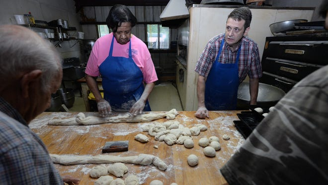 Lucille Pattain, Gregory Grayson join others as they make the fresh buns at Grayson's Barbecue.
