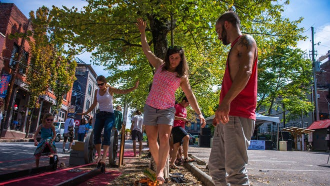 Leeann Johnson tries out a slackline demonstration while Alex Belue offers balance tips at the Lexington Avenue Arts and Fun Festival in September.