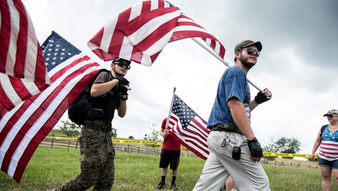 People carry American flags near a demonstration area at Gettysburg National Military Park on July 1, 2017.