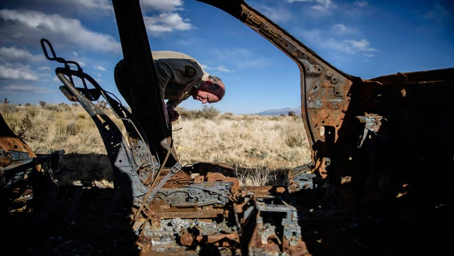 In this Feb. 23, 2018 photo, Lt. Keith Elder, of the Sandoval County Sheriff's Office, examines the rusted and burned out hull of a Nissan left on the side of a dirt road in the Rio Rancho Estates area west of the city.