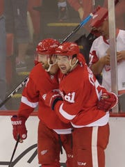 Red Wings forward Darren Helm and defenseman Xavier Ouellet celebrate during the first period Monday at Joe Louis Arena.