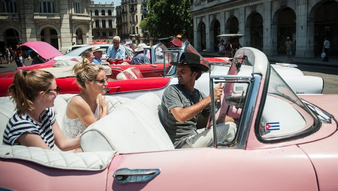 Visitors from the United States sit in a classic American car in Havana, on April 6, 2015. They will now be able to use U.S.-issued debit cards on the island.