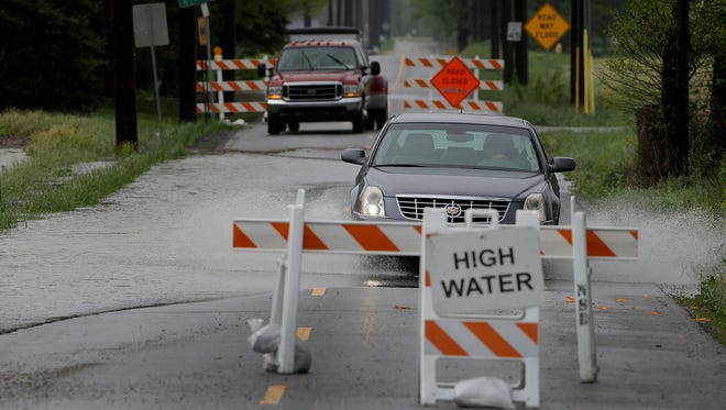 High water signs are ignored by motorists of the possible dangerous roads on Promise Road between 186th and 191st Streets Friday, May 5, 2017, morning in Noblesville.