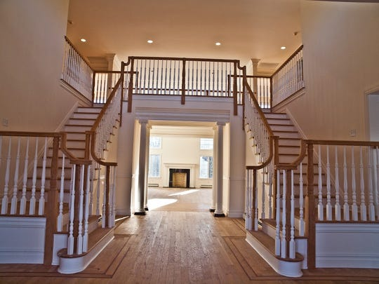 The grand foyer features a custom oak stairway.