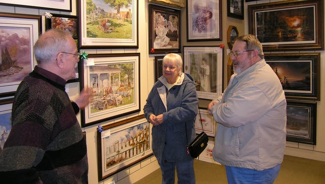 Clarence Scherer of Decorator's Gallery in Egg Harbor talks about artwork with Louise Boggs and Conrad Kustka, both of De Pere, at the Door County Christmas store at Bay Park Square mall. Several Door County retailers are sharing the space during the Christmas shopping season.