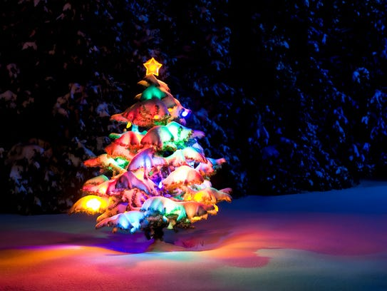 Snow covered Christmas tree with multi-colored lights