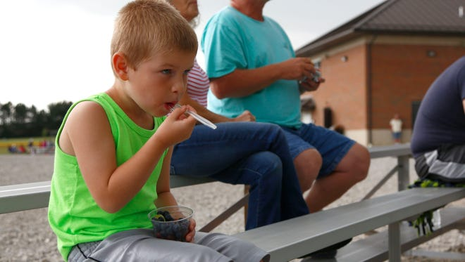 Isaiah Blust, 7, eats from a fruit cup while watching his brother play at the Ontario Baseball Complex on Thursday night. The fruit cup is one of many healthy snack option that are offered by the complex this year.