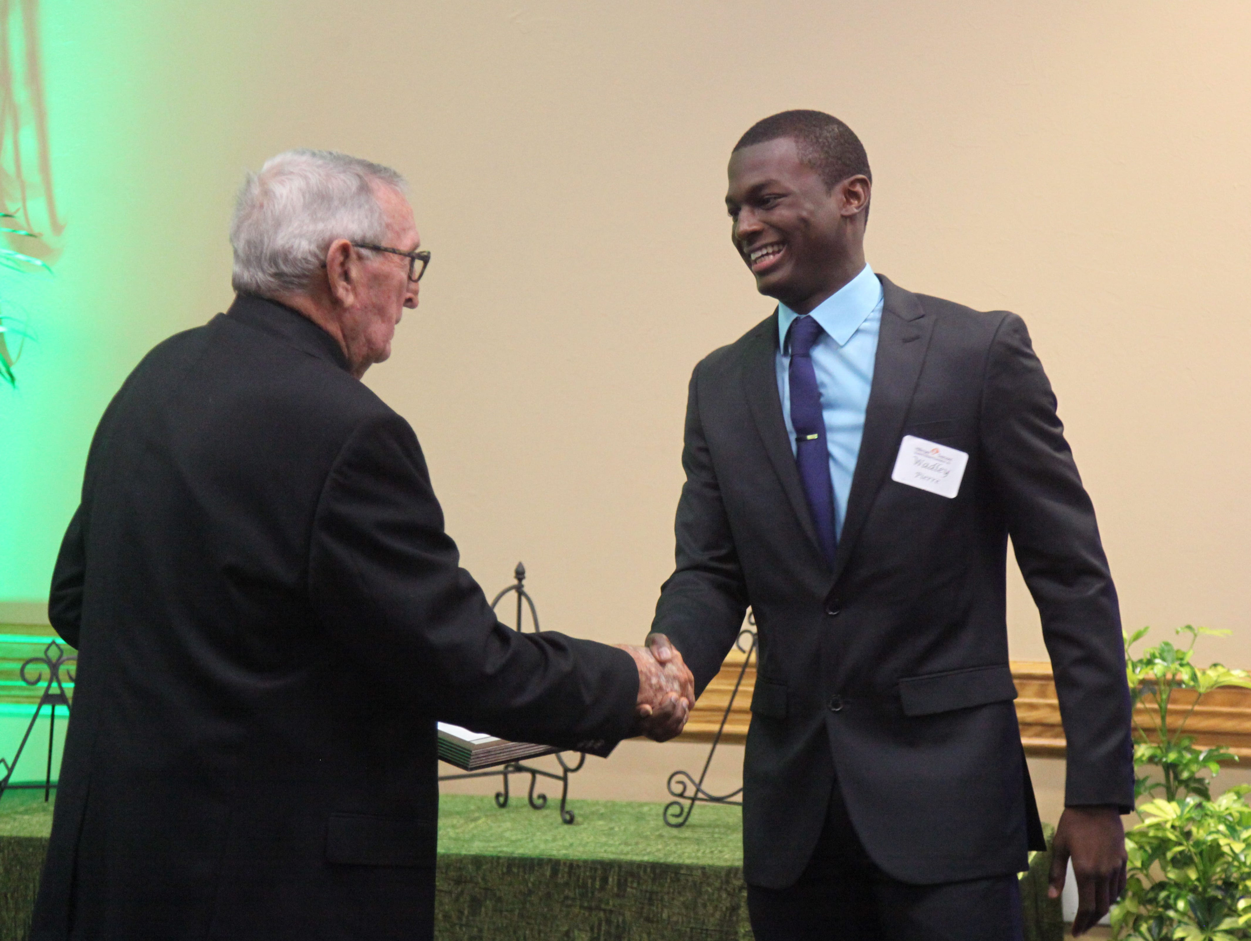 Wadley Pierre, of Lehigh High School, is congratulated by Elmer Tremont during the Hillmyer-Tremont scholarship banquet at FGCU's Cohen Center on Monday.