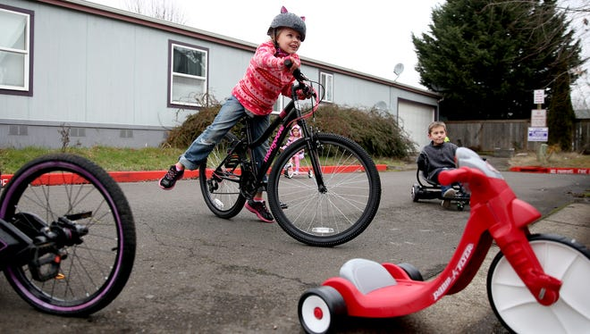 Madison Bear, 9, rides her new bicycle outside her grandparents' home with their neighbor Ryan Hofmann, 9, in Dec. 2017.